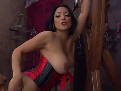 Dark haired dominatrix Kiara Mia in taut corset shows off her big boobs and bubble butt as she receives her rectal hole licked from behind by her slave boy in the dungeon. She loves rimming