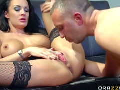 Gorgeous large titted babe Alektra Blue in black stockings spreads her legs on the edge of the couch to make her horny co-worker happy. He licks and fucks her vagina before she takes his prick in her arsehole