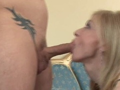 Blonde mom Nina Hartley fills her sexy mouth with a young man's thick dick