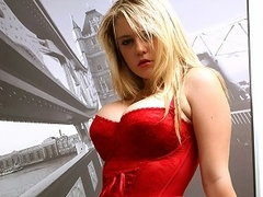 A blonde girl down bg breast and dressed in a tight corset is standing...
