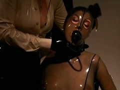 Blonde Goddess Makes Busty Resigned Brunette hair Wear Suffocating Latex Suit